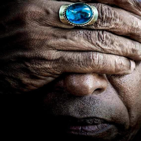 Image of a black man covering his eyes with one of his fingers having a blue ring